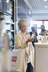 Woman shopping for perfume in airport duty free shop - CAIF10204