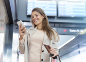Businesswoman with passport using cell phone in airport - CAIF10210