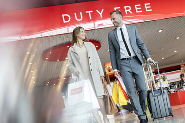 Business people leaving airport duty free shop with shopping bags and suitcase - CAIF10213