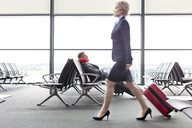 Businesswoman pulling suitcase past resting businessman with neck pillow in airport departure area - CAIF10216