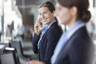 Portrait smiling customer representative talking on telephone at airport check-in counter - CAIF10219