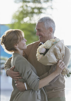 Smiling couple with flower bouquet hugging - CAIF10225