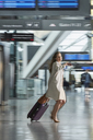 Businesswoman rushing pulling suitcase and checking the time in airport concourse - CAIF10228