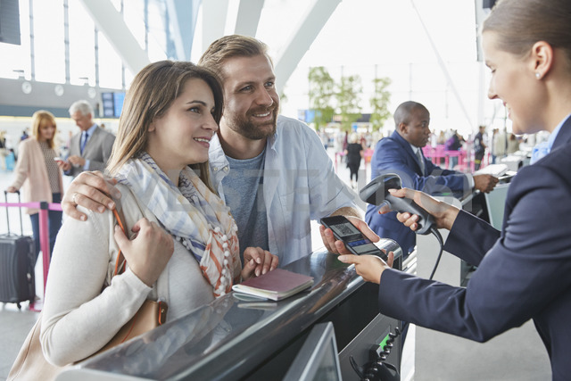 Customer service representative scanning smart phone QR code at airport check-in counter - CAIF10234