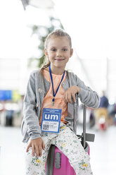Portrait smiling girl sitting on suitcase in airport - CAIF10240