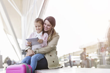 Mother and daughter using digital tablet outside airport - CAIF10246