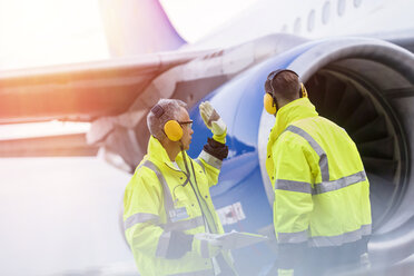 Airport ground crew workers talking near airplane - CAIF10264