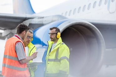 Air traffic control ground crew with clipboard next to airplane on tarmac - CAIF10267