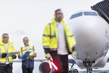 Air traffic controllers walking in front of airplane on airport tarmac - CAIF10270