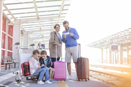Family with suitcases waiting at train station platform - CAIF10276