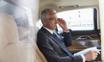 Businessman with paperwork riding in back seat of town car - CAIF10279