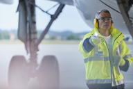 Air traffic controller with flashlight under airplane on airport tarmac - CAIF10285