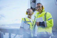 Portrait confident air traffic control ground crew workers with digital tablet near airplane on tarmac - CAIF10291
