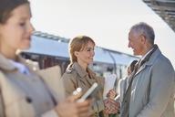 Businessman and businesswoman handshaking on sunny train station platform - CAIF10294