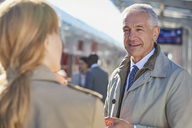 Businessman talking to businesswoman on train station platform - CAIF10297