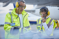 Air traffic control ground crew workers with clipboard talking on airport tarmac - CAIF10300