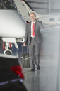 Smiling businessman pulling suitcase talking on cell phone in airplane hangar - CAIF10303