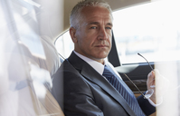 Pensive businessman riding in back seat of town car - CAIF10306