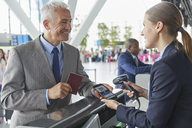 Customer service representative scanning smart phone QR code boarding pass at airport check-in counter - CAIF10309