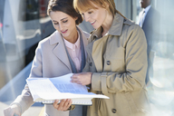 Businesswomen reading paperwork on sunny train station platform - CAIF10315