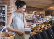 Woman grocery shopping smelling mushrooms - CAIF10327