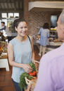 Smiling woman checking out at grocery store - CAIF10330