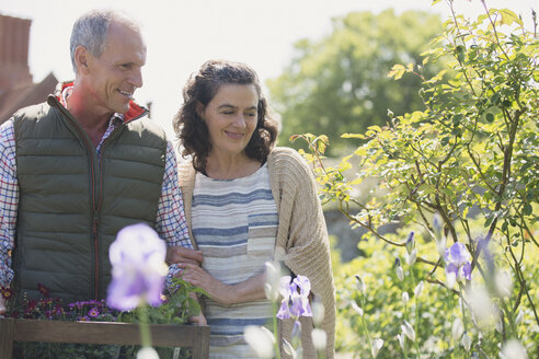 Smiling couple shopping for flowers in plant nursery garden - CAIF10351