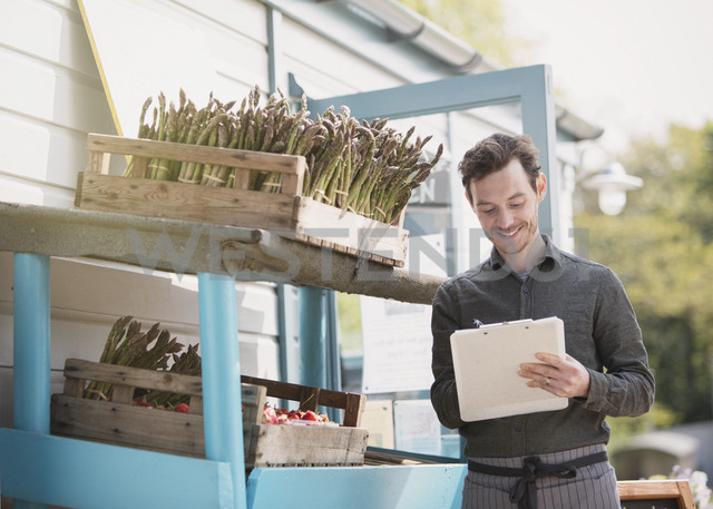 Farmerís market worker with clipboard checking inventory next to asparagus - CAIF10378
