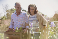 Smiling couple shopping for flowers in sunny plant nursery garden - CAIF10402