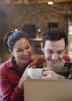 Smiling couple drinking cappuccino at laptop in cafe - CAIF10411