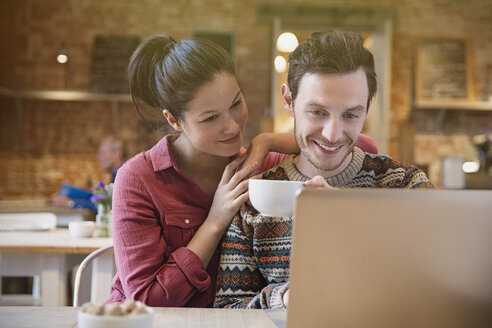 Smiling couple drinking coffee using laptop at cafe - CAIF10420