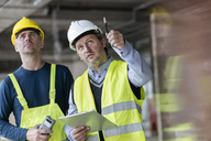 Male foreman and engineer with clipboard looking up at construction site - CAIF10450