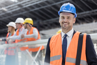 Portrait confident businessman in hard-hat at construction site - CAIF10453