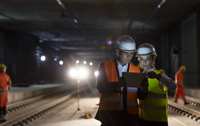Foreman and construction worker using digital tablet at dark underground construction site - CAIF10459