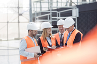 Foreman and engineers discussing paperwork at construction site - CAIF10462