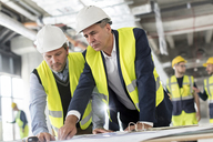 Male engineers viewing blueprints at construction site - CAIF10468