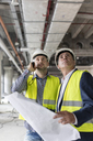 Male engineers with flashlight and blueprints looking up at construction site - CAIF10471