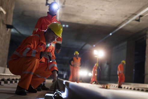 Male construction workers examining underground tracks at dark underground construction site - CAIF10474