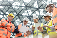 Foreman and construction workers using digital tablets in meeting at construction site - CAIF10483