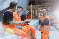 Construction workers eating lunch at construction site - CAIF10486