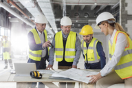 Engineers reviewing blueprints at construction site - CAIF10492