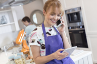 Smiling caterer working, talking on cell phone and using digital tablet in kitchen - CAIF10516
