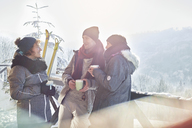 Skier friends talking, drinking coffee and hot cocoa apres-ski - CAIF10531