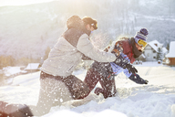 Playful couple enjoying snowball fight in snowy field - CAIF10558