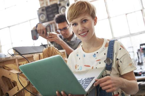 Portrait smiling female designer using laptop in workshop - CAIF10597