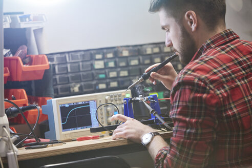 Male engineer assembling electronics, using soldering iron - CAIF10633