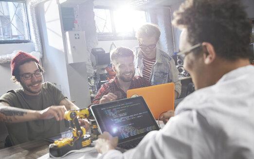 Computer programmers programming robotics in workshop - CAIF10636