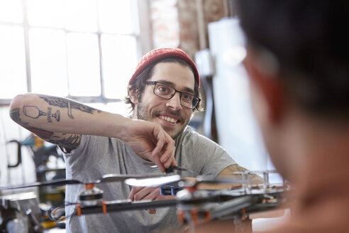 Smiling male designer with tattoos assembling drone - CAIF10648