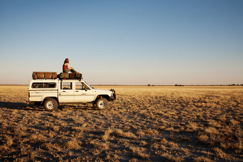 Side view of woman sitting on off-road vehicle at field - CAVF05204