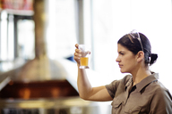 Woman examining beer in glass beaker while standing at brewery - CAVF05321